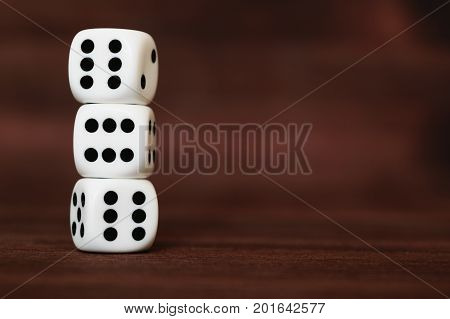 Three white plastic dices on each other on brown wooden board background. Six sides cube with black dots. Satan's number 666.