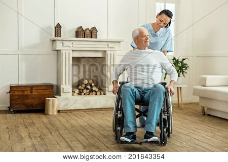 Mobility equipment. Positive nice senior man sitting in the wheelchair and moving forward while being partially paralyzed