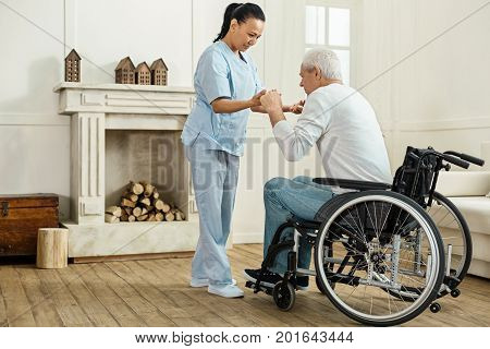 Be careful. Professional experienced female caregiver holding her patients hands and helping him to get up while looking after him