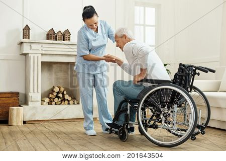 Medical equipment. Nice pleasant senior man using caregivers help and getting out from the wheelchair while wanting to sit on the sofa