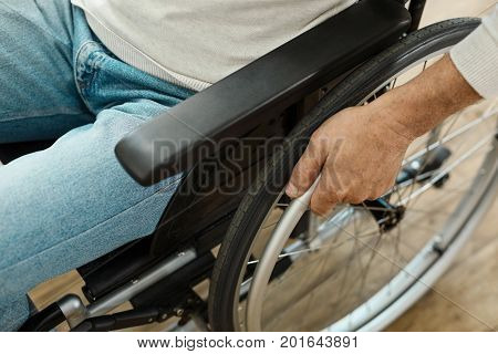 Staying mobile. Modern wheelchair being in use by a nice pleasant elderly man while being unable to walk