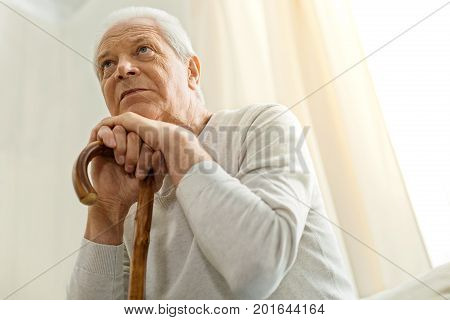 Old age. Thoughtful unhappy aged man holding a walking stick and leaning on it while thinking about his life
