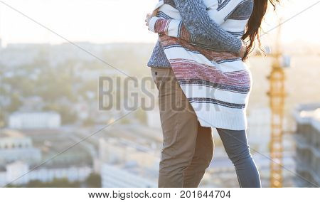 Young man and woman embrace outdoors on autumn sunset. Love and relationship concept