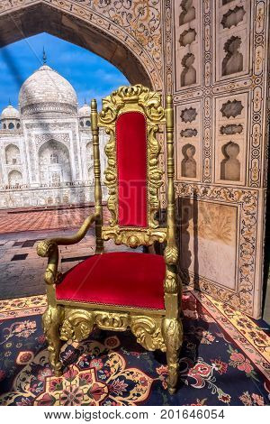 Red and gold armchair similar to the throne in the background of the mausoleum Taj Mahal.