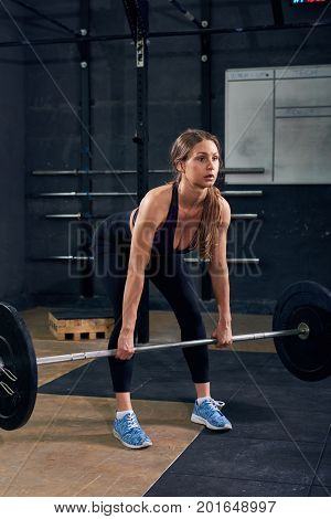 Portrait of strong young woman lifting heavy barbell during weights workout in modern gym