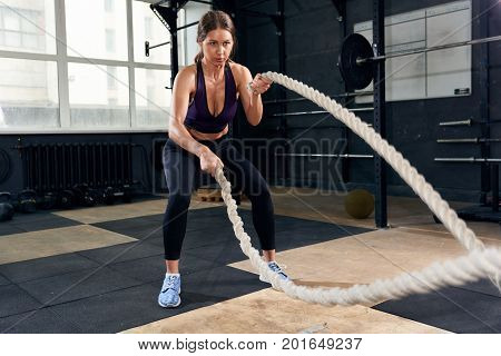 Portrait of strong young woman exercising with battle ropes during intense workout in modern gym