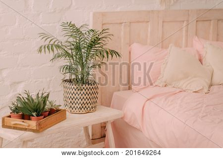 Flowers on a wooden table near the bed