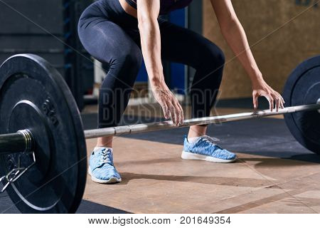 Low section portrait of unrecognizable young woman reaching out preparing to lift heavy barbell during weights workout in modern gym