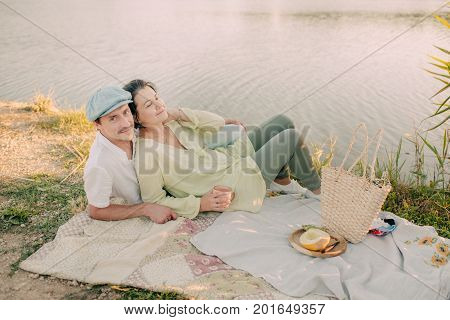 A girl with man on the river bank under the shining sun