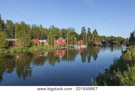 KOKKOLA, FINLAND ON JULY 07. View of a channel, red wooden boathouses by the seaside. Flowers this side on July 07, 2017 in Kokkola, Finland. Evening and bright sunshine. Editorial use.