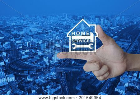 Hammer and wrench with house icon on finger over modern city tower street and expressway Home service concept