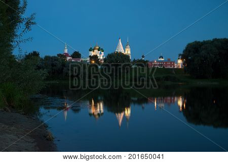 Kolomna Moscow Region. Beautiful View Of Various Temples And Belltower On Assumption Cathedral Square Under Blue Sky By Embankment Reflection River.