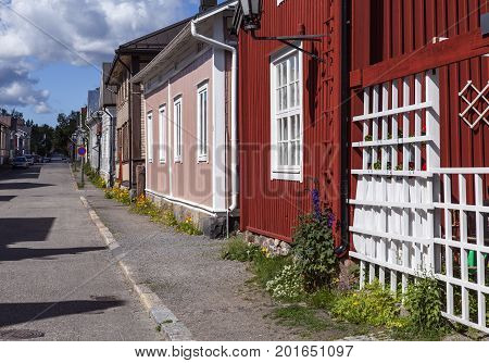 KOKKOLA, FINLAND ON JULY 07. Street view of wooden buildings, flowers, sidewalk on July 07, 2017 in Kokkola, Finland. Lamppost and signs. Editorial use.