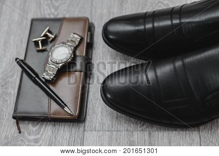 Businessman accessories. Man's style. Shoes with watch and cuff