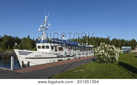 KOKKOLA, FINLAND ON JULY 07. View of Jenny moored by the port on July 07, 2017 in Kokkola, Finland. Channel, sidewalk and bushes in the surrounding. Editorial use.