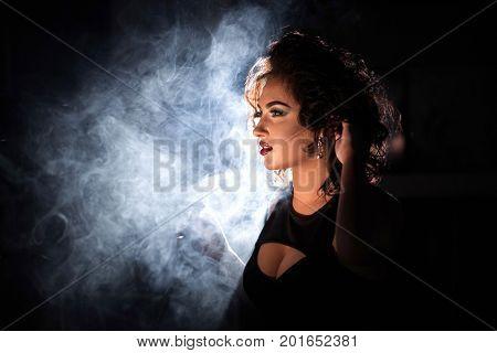 Close-up shot of a woman in a hookah smoke wearing deep neckline dress