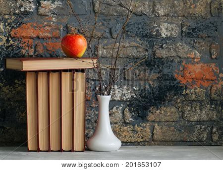 Old books apple and brunches in vase. Autumn mood reading concepts