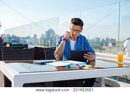 Interesting information. Modern young man sitting at a table of a cafe and focusing his attention on a screen of his digital tablet while working on home assignment and getting ready for tomorrow.