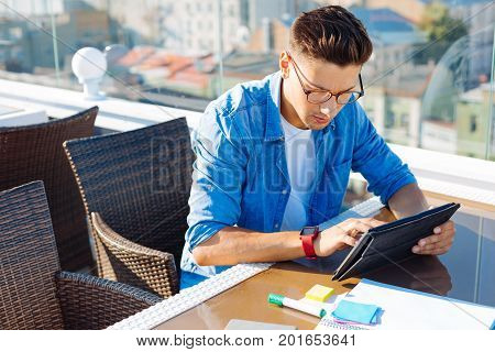 What a cool piece of information. Top view on a young man focusing his attention on a screen of tablet computer while doing his homework and surfing the net on a terrace of an urban cafe.