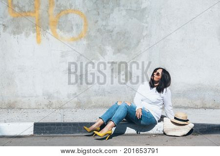 Young fashion woman wearing ripped jeans, colorful heel shoes and straw accessories posing over gray concrete city wall. Plus size model.