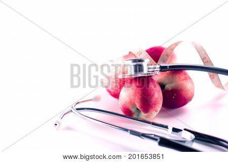 red nectarine fruit with stethoscope auscultating for healthy