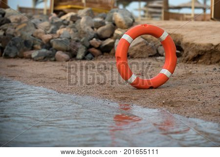 Life ring orange and white saver protection on water at sand beach in summer on background of stack of stones