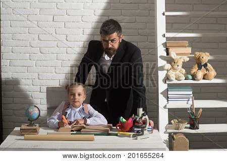 Family By Desk With School Supplies. Girl And Her Father
