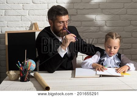 Schoolgirl And Her Tutor With Serious Faces Write In Notebook