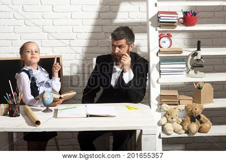 Kid And Teacher Sit At Desk With School Supplies