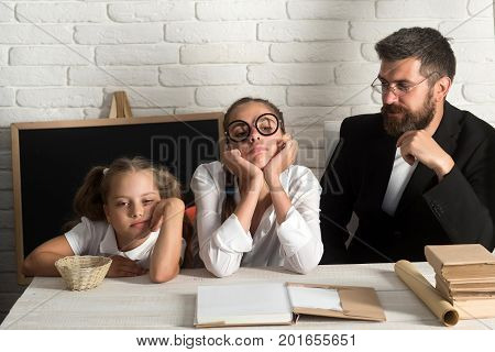 Girls and bearded man sit at desk with books. Kid elder sister and tutor with bored and concerned faces. Teacher and schoolgirls on classroom background. Home schooling and back to school concept