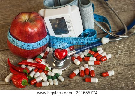 Red apple with measuring tape to measure length. Treatment of obesity and diabetes measurement of blood pressure