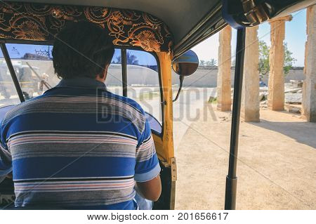 Hampi, India - November 11, 2012: Point of view shot from inside a moving tuk tuk. Street scene with ancient ruin of Hampi in motion blur on sandy and dusty road