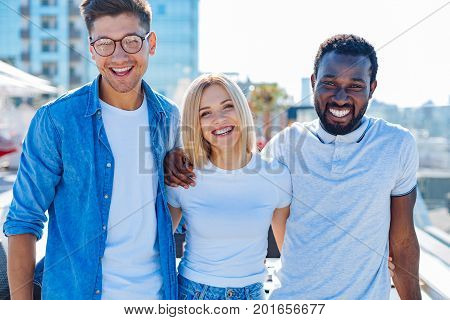 Memorable time. Waist up shot of a millennial friends embracing and grinning broadly while looking into the camera and posing for a photo together outdoors.