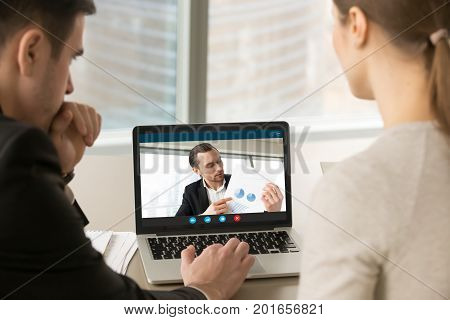 Businesspeople participate video conference looking at laptop screen during virtual meeting with investor for startup, discussing financial document online, videocall webcam app for business, close up