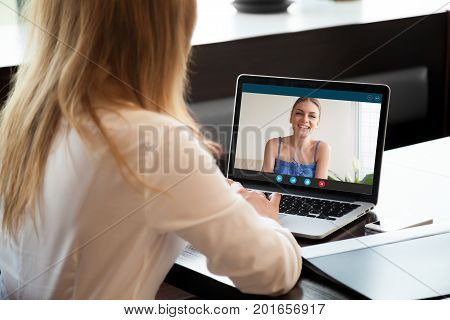 Two young women chatting online by making video call on laptop, using videoconferencing app for communication with distance friend, studying online course, virtual learning, close up rear view
