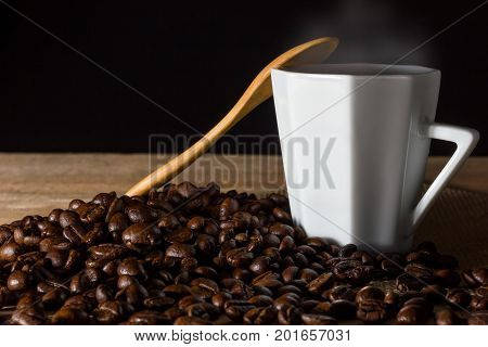 Low key coffee in the darkness. Roasted coffee beans on a wooden table with a glass of white ceramic and a wooden spoon.