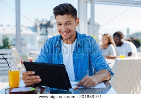 How is it possible. Happy self employed guy in casual smiling while looking at a screen of his tablet computer and reading news on the internet.