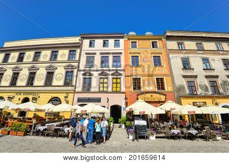 Lublin, Poland - August 10, 2017: Beautiful street and old colorful buildings in the old town of Lublin, Poland. Center of Lublin town. Old buildings and small street cafes at old Lublin town.