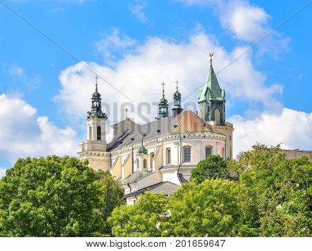 Lublin, Poland - August 10, 2017: Beautiful view of old church green trees and bright blue sky, old city center. The Metropolitan Cathedral of St. John the Baptist and the Evangelist in Lublin, Poland