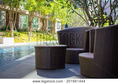 Chairs and table near swimming pool with clean blue water