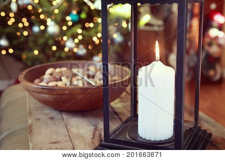 Christmas candle over background of Christmas tree lights, focus on candle wick