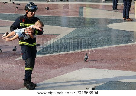 BARCELONA/SPAIN - 26 AUGUST 2017: Firefighter holding a child in Plaza de Catalunya on the massive protest `I am not scared` against terrorism and islamophobia after the attack on Rambla.