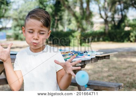 Charming boy posing expressively with deflated flying balloon on background of garden and table with studies.