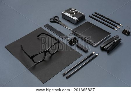 A set of black office accessories, glasses and old camera on gray background. Flat lay. Still life. Mock-up