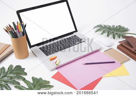 designer office desk with notebook and computer crayon leaves. Top View table from above with flat lay.