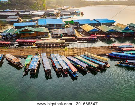 Sangkhlaburi - March 05 2017: The scenery of floating village and tourist boats and a part of temporary bamboo bridge the river in Sangkhlaburi District Kanchanaburi Province Thailand in the early morning.
