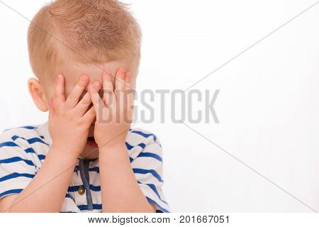 Portrait of a small toddler blond boy in a striped shirt hiding himself with hands.. Child crying. Emotions.