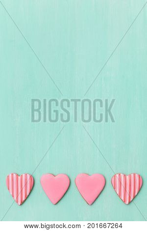 Top view on four little pink gingerbread cookies in shape of hearts on turquoise background. Flay layout. Love Valentines's day concept