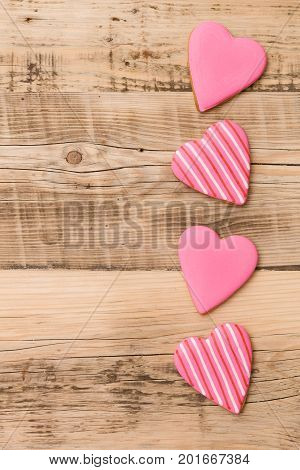 Top view on four little gingerbread cookies in shape of hearts on retro wooden background. Flay layout. Love Valentines's day concept