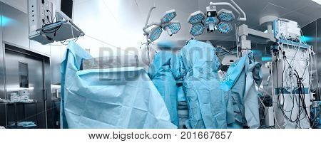 Panoramic image of the modern operating room with the personnel working with the patient.